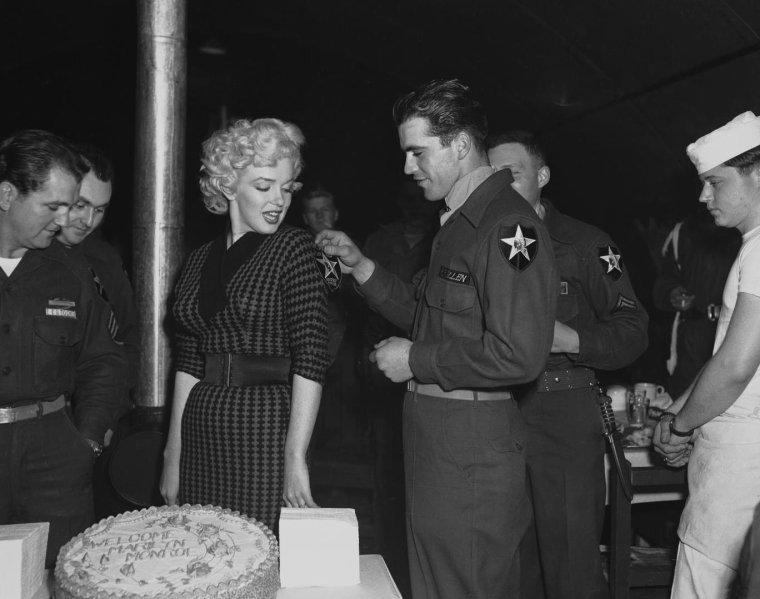 1954 / Lors de sa tournée de chants en Corée pour remonter le moral des troupes de G.I.'s, Marilyn est conviée à un dîner organisé en son honneur, par pas moins de 55 officiers ; elle jouera le temps de quelques photos les cantinières, et pour l'occasion, un gâteau lui sera confectionné...