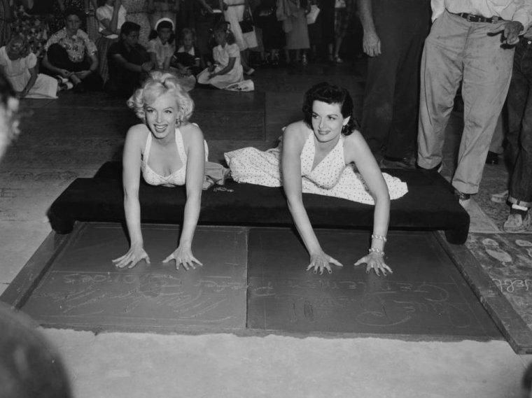 """1953 / Le 26 juin 1953, pendant la campagne publicitaire de « Gentlemen prefer blondes », Marilyn et Jane RUSSELL laissent leurs empreintes de mains et de pieds en face de ce célèbre cinéma, le """"Grauman's Chinese Theatre"""",  faisant suite à une tradition créée par Mary PICKFORD et Douglas FAIRBANKS, au milieu des années 1920, lorsqu'ils avaient malencontreusement pataugé dans le ciment frais répandu à cet endroit. (part 2, voir TAG)."""