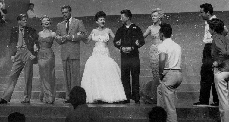 "1954 / Final de la comédie musicale ""There's no business like show business"", où Johnnie RAY, Mitzi GAYNOR, Dan DAILEY, Ethel MERMAN, Donald O'CONNOR et Marilyn, chantent la chanson du même titre."