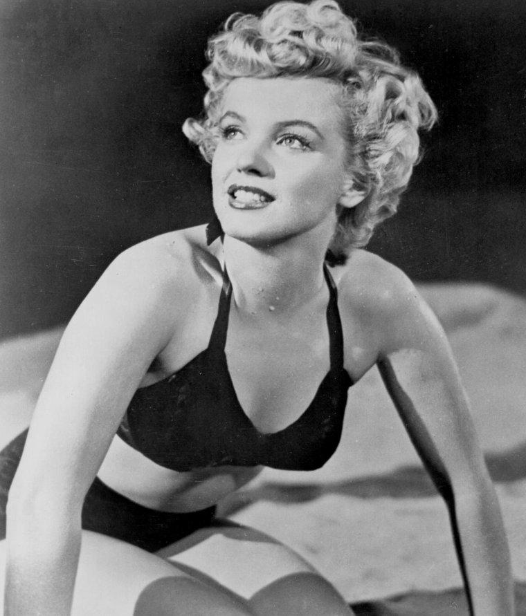 """1952 / Marilyn en maillot sur la plage aux côtés de Keith ANDES lors du tournage du film """"Clash by night""""."""