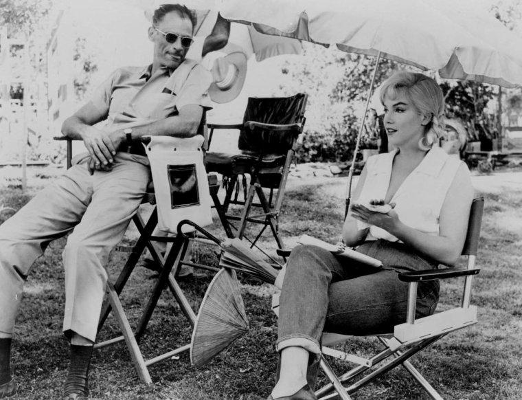 """1960 / Marilyn et MILLER lors du tournage du film """"The misfits""""... / TOURNAGE CAUCHEMARDESQUE /  « The misfits » est le vingt-neuvième et dernier film de Marilyn, si l'on ne tient pas compte de « Something's got to give », resté inachevé. Arthur MILLER avait écrit une nouvelle, qui parut dans le magazine """"Esquire"""" en 1957. Lorsqu'il vivait à Reno en attendant son divorce et avant d'épouser Marilyn, il avait rencontré des hommes qui, comme Clark GABLE et Montgomery CLIFT dans le film, capturaient des chevaux sauvages, qu'ils revendaient ensuite et dont on faisait de la nourriture pour animaux. MILLER adapta la nouvelle pour en faire un scénario, Sam SHAW lui ayant suggéré que ce sujet ferait un excellent film pour Marilyn. Pour cela MILLER dut développer le personnage de Roslyn, trop falot pour la nouvelle. Il retravailla le script jusqu'au dernier jour du tournage. Il modifiait sans arrêt la fin et avait du mal à décider quel cowboy l'emporterait dans le coeur de la jeune femme. Montgomery CLIFT n'était pas le seul à penser que Clark GABLE, qui était un homme mûr, devrait tenir le rôle principal. Au début de 1958, MILLER proposa la production du film à son ami Frank TAYLOR, qui suggéra d'envoyer le scénario à John HUSTON et de lui en proposer la réalisation. On rassembla une équipe prestigieuse, dont Montgomery CLIFT et Eli WALLACH, tout deux amis de Marilyn. Mais MILLER fit encore mieux et réussit à convaincre Clark GABLE, en lui expliquant qu'il s'agissait « d'une sorte de western de l'Est qui traitait de l'absence de signification de nos vies et peut-être aussi de la façon dont nous sommes arrivés où nous en sommes ». Au début, Marilyn considérait le film comme un cadeau d'amour. Mais lorsque le tournage commença, début 1960, les relations entre MILLER et Marilyn avaient atteints leur point de rupture. Dans son autobiographie Arthur MILLER écrivit :  « Dès le commencement de « The misfits », il me fut impossible de nier que, s'il existait une clé pour le désespoi"""