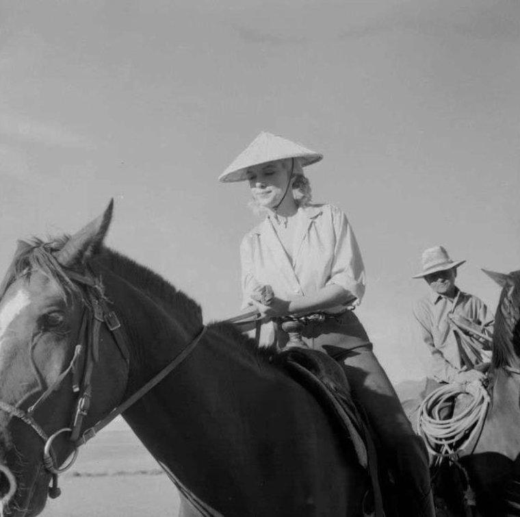 """1960 / Marilyn pas très à l'aise, sous le soleil torride dans le désert du Nevada, prenant quelques leçons pour monter à cheval, pour les besoins d'une scène du film """"The misfits""""."""