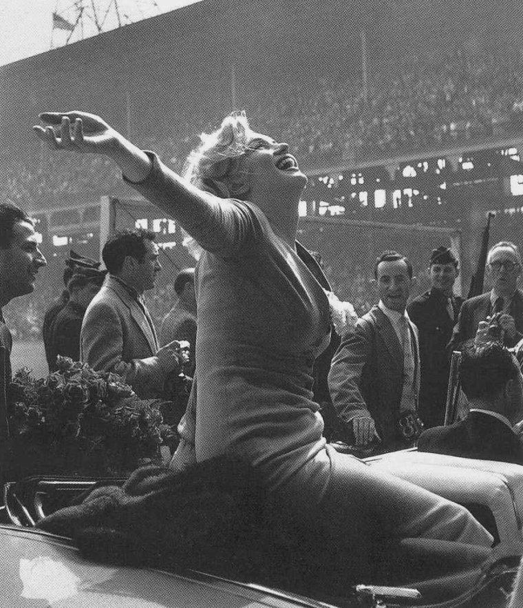 """1957 / Marilyn est acclamée par la foule en entrant dans le stade d'""""Ebbets field"""", à New-York, afin de donner le coup d'envoi d'un match de football opposant les Etats-Unis à Israël. (part 4, voir TAG). (certaines photos signées Sam SHAW)."""