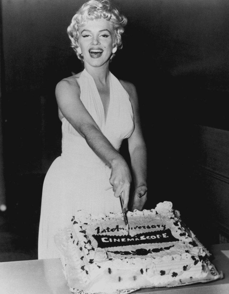 """1954 / Marilyn aux côtés de DiMAGGIO ou encore Walter WINCHELL, sur le tournage du film """"The seven year itch"""", coupe un gâteau symbolisant le premier anniversaire du cinémascope ; une visite surprise adviendra sur le plateau ; celle de Gina LOLLOBRIGIDA."""
