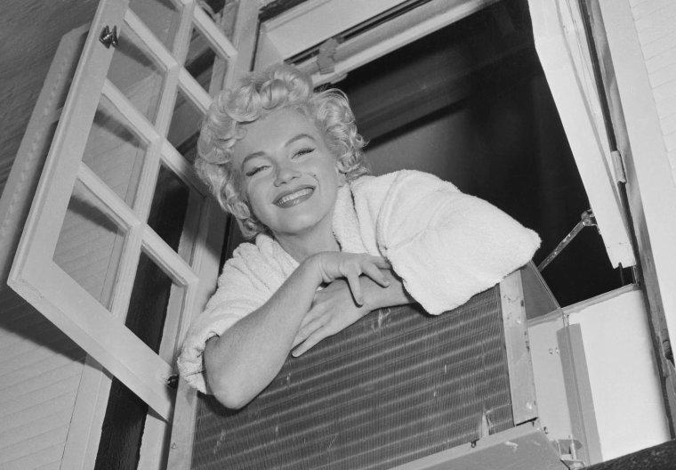 """1954 / Marilyn à la fenêtre dans un """"brownstone"""" typique de New York, situé au 164 East 61st Street, lors du tournage du film """"The seven year itch"""" ; certaines photos signées George BARRIS et Bob HENRIQUES."""