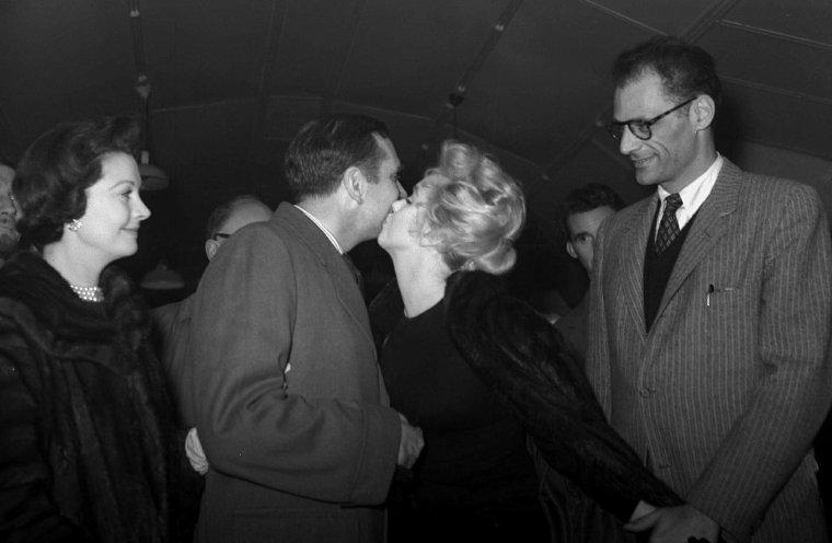 """1956 / 22 Novembre... Marilyn vient de terminer le film """"The prince and the showgirl"""", Vivien LEIGH et son mari Laurence OLIVIER raccompagnent le couple MILLER à l'aéroport pour leur départ de Londres... Ils firent tous bonne figure, alors que leur vie à chacun avait été bouleversée depuis qu'ils s'étaient retrouvés là en juillet : Vivien LEIGH avait perdu son bébé et par là même, toute chance de sauver son mariage. Laurence OLIVIER avait raté l'occasion d'une renaissance personnelle qu'il espérait réaliser avant la cinquantaine. Arthur MILLER avait compris que la vie avec Marilyn allait être différente de tout ce qu'il avait imaginé. Et Marilyn, toujours bouleversée par ce qu'elle avait lu dans le cahier d'Arthur, avait toutes les raisons de croire que tant son mariage que son premier film indépendant (Marilyn MONROE Productions) étaient voués à l'échec. Pendant presque deux ans, Marilyn ne tournera plus de films."""