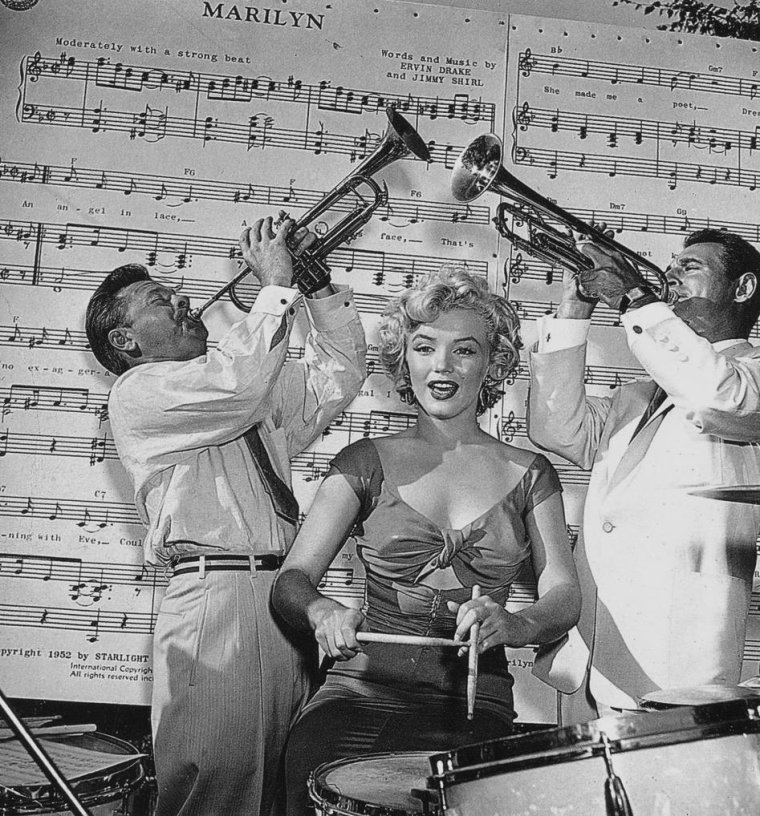 "1952 / Marilyn se rendit à San Diego à une réception organisée par la Fox chez le chef d'orchestre Ray ANTHONY pour l'enregistrement de la chanson « Marilyn » par Ervin DRAKE et Jimmy SHIRL. Marilyn, arrivée par hélicoptère, ravit les invités en jouant des percussions sous la direction de  Mickey ROONEY. / PAROLES DE LA CHANSON ""Marilyn"" / An angel in lace, A fabulous face, That's no exaggeration, That's my Marilyn.  No gal, I believe, Beginning with Eve, Could weave a fascination like my Marilyn.  She made me a poet, Thinking up romantic themes, Though she may not know it, she's all mine in my dreams.  I've planned everything, The church and the ring, The one who doesn't know it yet Is Marilyn.  She hasn't said ""Yes"" I have to confess: I haven't kissed, or even met My Marilyn.  But if luck is with me She'll be my bride forevermore; I'll be marryin', carryin' Marilyn  through my door     But if luck is with me She'll be my bride forevermore; I'll be marryin', carryin' Marilyn  through my door."