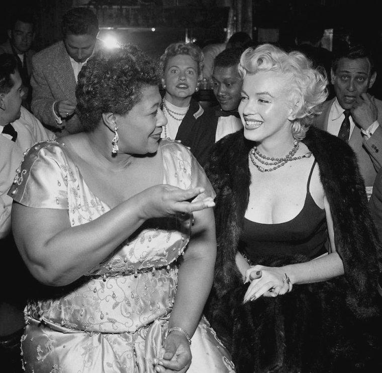 """1954 / « J'ai une vrai dette envers Marilyn MONROE. » C'est Ella FITZGERALD qui parle. En effet, dans le milieu des 50's (1954), le """"Mocambo"""" est le club de jazz à la mode de Los Angeles. Frank SINATRA, y a fait ses débuts en vedette en 1943. Mais voilà, l'endroit n'accueille que des artistes blancs. « Marilyn a personnellement appelé le patron du """"Mocambo"""", poursuit Ella. Elle lui a dit qu'elle voulait que je sois programmée immédiatement. Et que si c'était le cas, elle prendrait une table devant la scène tous les soirs. »  Le taulier accepta et la star tint promesse devant un parterre quotidien de journalistes. Une publicité dont le """"Mocambo"""" profita amplement, avant que le talent d'Ella né fasse son propre office et que sa carrière décolla. Une belle amitié naquit entre les deux femmes."""