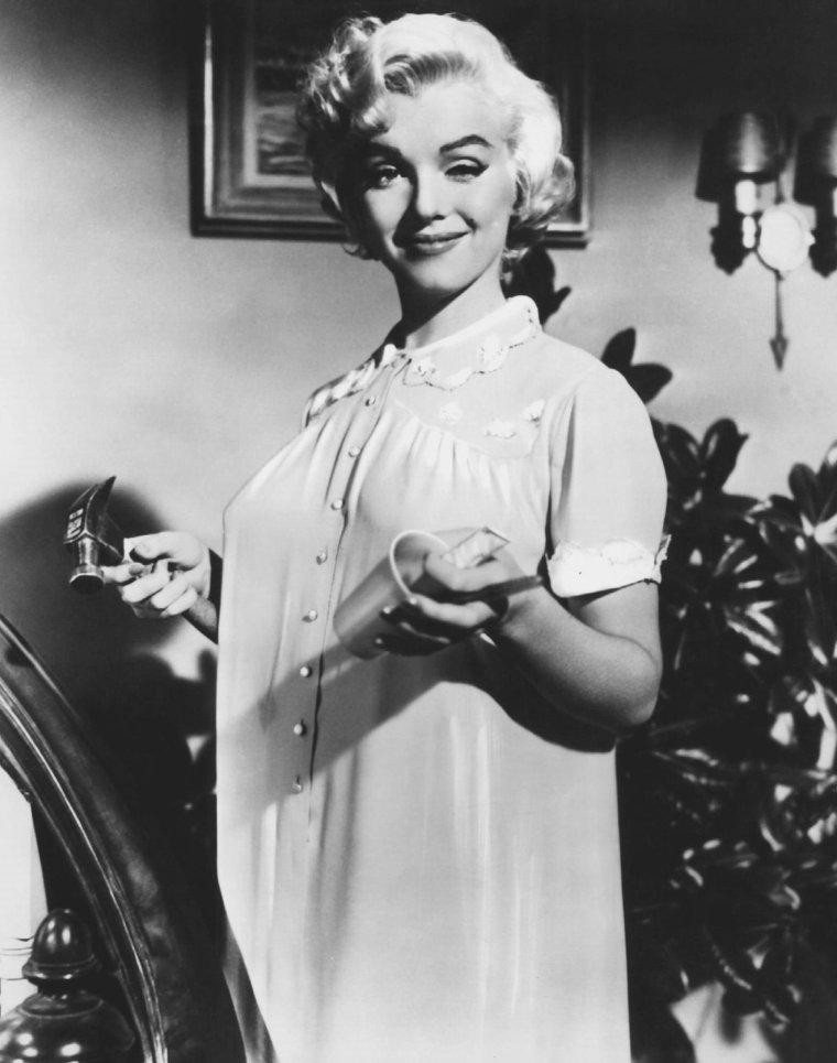 """1954 / Marilyn en chemise de nuit et mules, lors du tournage du film """"The seven year itch"""", sous la direction, pour les besoins d'une scène, du metteur en scène Billy WILDER."""