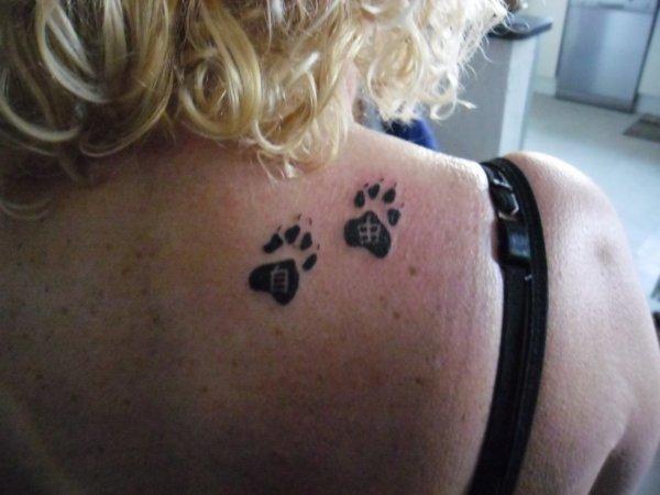 """Pattes de chat avec """"Liberté"""" en kanji à l'intérieur des empreintes"""