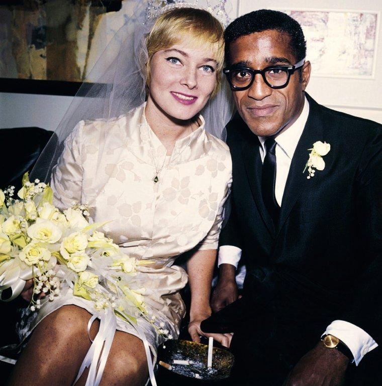 """COUPLE DE LEGENDE / May BRITT et Sammy DAVIS Jr (mariés le 13 Novembre 1960 - divorcés le 20 Décembre 1968, une fille) / En 1960, Sammy DAVIS Jr crée la polémique en épousant l'actrice d'origine suédoise May BRITT, dans une Amérique encore profondément ségrégationniste. Il reçoit des lettres de menaces après avoir été choisi pour jouer à Broadway dans la comédie musicale """"Golden Boy"""" en 1964. Ce qui ne semble pas ternir l'enthousiasme des fans : le spectacle est un succès (au début) mais s'arrête finalement après quelques représentations. Les mariages interraciaux sont alors interdits par la loi dans 31 États, des lois abolies par la Cour suprême américaine en 1967. May BRITT donne naissance à une fille et le couple adopte deux autres enfants. Sammy, qui enchaîne les spectacles, passe peu de temps avec sa femme. Il avoue également entretenir une relation avec la chanteuse Lola FALANA (sa partenaire dans """"Golden Boy""""), ce qui précipite le divorce du couple prononcé en 1968."""