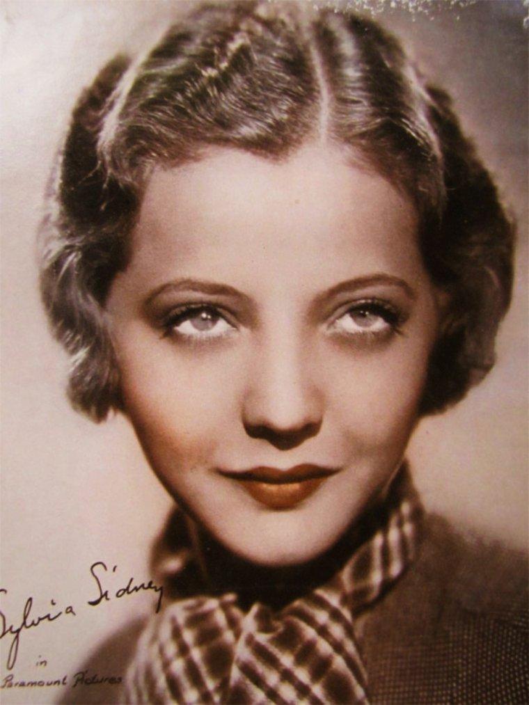 """NEWS / Sylvia SIDNEY est une actrice américaine, née le 8 août 1910 dans le Bronx, New York, et décédée d'un cancer de l'½sophage le 1er juillet 1999 à New York (États-Unis). / MINI-BIO / Fille d'immigrés juifs venus de Russie et Roumanie, elle joue sur scène à Washington à seize ans avant de se faire remarquer à Broadway (Dictionnaire du cinéma américain, Larousse, 1988). Engagée par le prestigieux studio Paramount en 1931, elle côtoie Marlène DIETRICH, Carole LOMBARD, Kay FRANCIS, Mäe WEST, Claudette COLBERT, autres stars féminines de la firme dans les années trente. Selon Christian VIVIANI, elle """"suggère idéalement la jeune fille d'origine pauvre, en détresse, type classique du cinéma muet qu'elle prolongea pour un temps"""". Spécialisée dans les rôles de victimes comme Fay WRAY, elle trouve son meilleur rôle dans cette veine en interprétant une mère célibataire dans """"Jennie Gerhardt"""" (1933) d'après Theodore DREISER. Elle s'illustre également dans """"Madame Butterfly"""", """"Mary Burns, la fugitive"""", """"Princesse par intérim""""... Elle enchaîne les collaborations prestigieuses avec Rouben MAMOULIAN (""""Les Carrefours de la ville""""), Josef Von STERNBERG (Une Tragédie américaine d'après DREISER), King VIDOR, Mitchell LEISEN, Wesley RUGGLES, Henry HATHAWAY (""""La Fille du bois maudit""""), Alfred HITCHCOCK, William WYLER, plus tard Frank LLOYD, William DIETERLE et Lewis MILESTONE. Surtout Fritz LANG lui offre trois de ses films les plus célèbres : """"Furie"""", """"J'ai le droit de vivre"""" et """"Casier judiciaire"""". Sylvia SIDNEY, logiquement, mène une grande carrière de séductrice à l'écran, passant de Gary COOPER et Cary GRANT à Henry FONDA, collectionnant les jeunes premiers (Fredric MARCH, Robert YOUNG, Herbert MARSHALL, Melvyn DOUGLAS) et quelques durs (George RAFT, Spencer TRACY, Humphrey BOGART, James CAGNEY), qui se clôt avec John HODIAK. Elle interprète aussi bien les héroïnes de Dashiell HAMMETT et de Victor HUGO (rôle de Fantine). Au début des années 1950, l'actrice se consacre presque ex"""