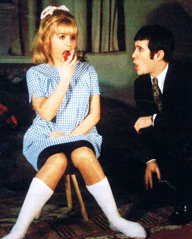"""COUPLE DE LEGENDE / Sophie DAUMIER et Guy BEDOS / Mini-bio / Elle débute au cinéma en 1955, dans """"Paris canaille"""", sous le nom de scène de « Betty DAUMIER ». Au début des années 1960, elle a une liaison avec le rocker Vince TAYLOR. En 1963, elle tourne """"Dragées au poivre"""", film musical, aux côtés de Claude BRASSEUR et de Francis BLANCHE, et où elle rencontre Guy BEDOS, déjà croisé au théâtre dans """"Cyrano de Bergerac"""". À cette époque, elle a un fils de 7 ans, Philippe, qui chante d'ailleurs une des chansons du film, """"Lili Gribouille"""", et que Guy BEDOS reconnaîtra plus tard. Philippe sera atteint plus tard de la même maladie que sa mère à l'âge de 40 ans. Elle perce vraiment au théâtre dans """"Patate"""", de Marcel ACHARD, qu'elle joue pendant six ans. C'est à cette époque que, sur les instances de celui-ci, elle se choisit un nouveau prénom, Sophie, et un nom de scène définitif, DAUMIER, nom de jeune fille de sa mère. Guy BEDOS et Sophie DAUMIER vont finalement unir leurs destins à l'occasion du spectacle """"Milord L'Arsouille"""". Ils se marient en 1965. Leur carrière commune durera une dizaine d'années. Ils interprètent ensemble de nombreux sketchs, écrits par Jean-Loup DABADIE, notamment « La Drague » (1972), qui connut un immense succès populaire et qui reste la référence de leurs duos, « Tête-bêche » ou « Les Vacances à Marrakech ». Sophie DAUMIER exprimait ainsi ses talents de comédienne, composant avec aisance des personnages de jeune femme tour à tour drôle, peste, ironique, tendre, grimaçante ou boudeuse. Après son divorce d'avec Guy BEDOS en 1977, Sophie DAUMIER poursuit sa carrière de son côté, jouant notamment dans """"Une histoire simple"""" (1978), de Claude SAUTET. Deux ans plus tard, elle publie des souvenirs teintés d'amertume : """"Parle à mon c½ur, ma tête est malade"""". Atteinte, comme sa mère et son fils, par """"la chorée de Huntington"""", maladie génétique qui entraîne une lente dégénérescence neuronale irréversible, elle est contrainte de réduire ses activités. En 1988"""