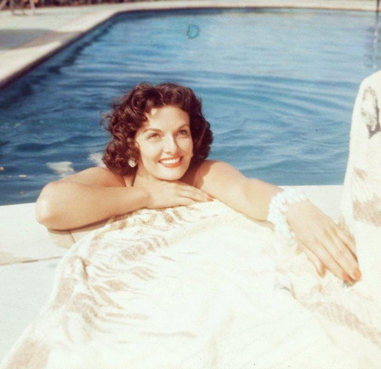 VIE PRIVEE / Jane RUSSELL eut trois maris : Bob WATERFIELD, un ancien joueur de football américain, entré au Hall of Fame (mariés le 24 avril 1943, divorcés en juillet 1968), l'acteur Roger BARRETT (mariés le 25 août 1968, décédé le 18 novembre 1968) et l'agent immobilier John CALVIN PEOPLES (mariés le 31 janvier 1974, décédé le 9 août 1999). Ces derniers vécurent à Sedona en Arizona. Dans son autobiographie de 1985, l'actrice révèle qu'elle fut enceinte à l'âge de 19 ans. S'ensuivit un avortement illégal, qui fut si mal mené que sa vie fut en danger quelques jours. En l'examinant aux urgences de l'hôpital, le médecin s'exclama « quel boucher vous a fait ça ! ? ». Après ces évènements, Jane RUSSELL fut incapable d'enfanter. Elle milita alors contre l'avortement. En février 1952, WATERFIELD et RUSSELL adoptent donc une petite fille, Tracy, puis un bébé de 15 mois, Thomas ; en 1956, ce fut un bébé de neuf mois, Robert John. En 1955, elle fonde la World Adoption International Fund (WAIF), une organisation chargée de placer les enfants dans les familles, qui fait beaucoup pour l'adoption d'enfants étrangers par les Américains. Bien que son image à l'écran fut celle d'une pin-up provocante, sa vie privée ne connaissait pas de scandales, contrairement à ce qui se passait pour certaines autres actrices de cette époque (Lana TURNER par exemple). Dans son autobiographie, elle dit avoir échappé à deux tentatives de viol, sans traumatisme. Elle affirme aussi que son premier mariage fut détruit par des soupçons d'adultère (des deux côtés) et la violence, qu'elle était alcoolique dès son adolescence. En outre elle révèle que la religion chrétienne l'a aidée à se régénérer. Au sommet de sa carrière, Jane RUSSELL fonde le Hollywood Christian Group, qui se rassemble une fois par semaine pour étudier la Bible, chez elle. De grandes célébrités s'y rendent. Jane RUSSELL, républicaine engagée, participe à la campagne et à l'élection de EISENHOWER, aux côtés de Lou COSTELLO, Dick POWELL