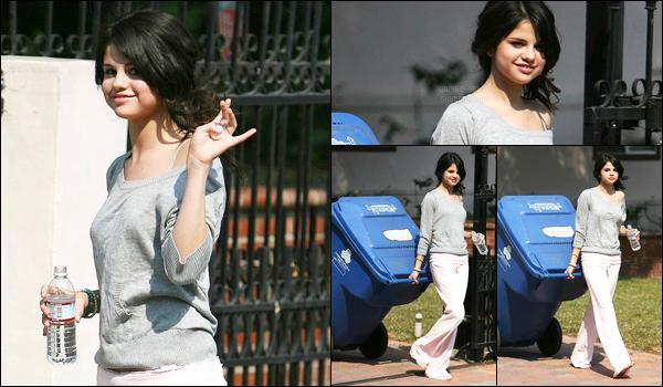 11.07.08 ─ Selena Gomez a été photographiée pendant qu'elle sortait de chez elle la poubelle, dans Los Angeles.Selena G qui était sûrement encore vêtue de son pyjama déposée sa poubelle au bout de chez elle. Elle était quand même souriante et fais un signe.