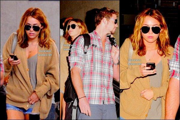 . 21.09.10 - Miley,scotchéà son portableaccompagné de Liam à l'aéroport de LAX. .