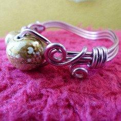 Bracelet en fil d'aluminium rose et perle de céramique.