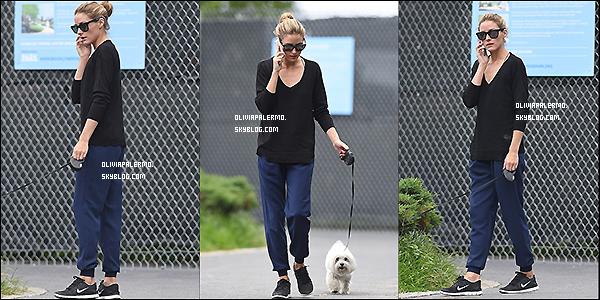 . 03/08/14 : Olivia habillée d'un jogging, d'un sweatshirt noir et de baskets Nike pour faire une promenade avec son petit chien. .