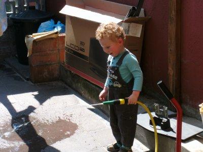 voici mon fils en train de nettoyer la cour av le tuyau d arrosage