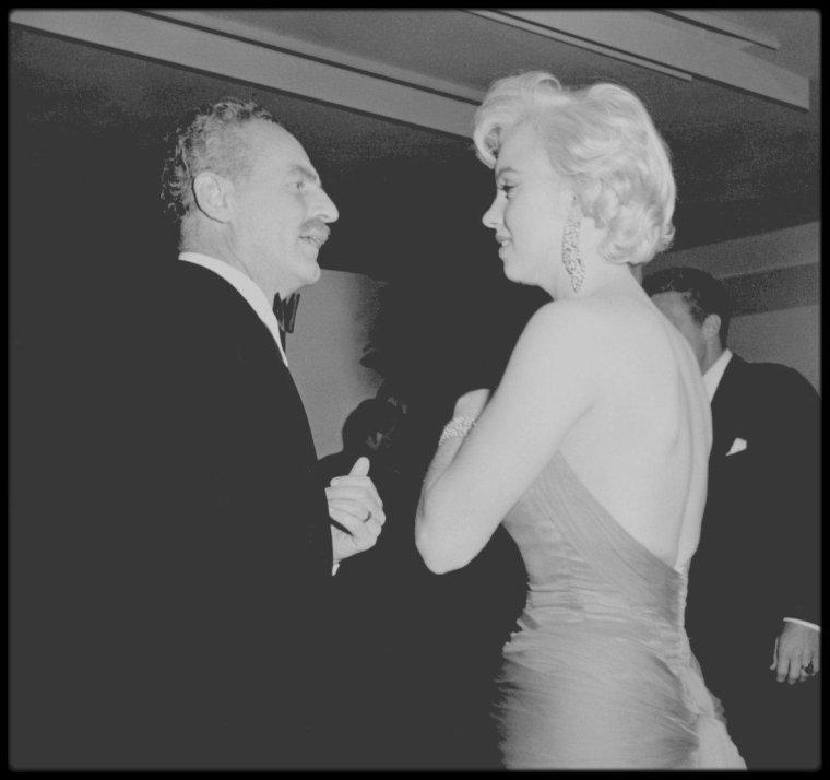 """1954 / Photos Sam SHAW... Pour fêter la fin du tournage de « The seven year itch », Charles FELDMAN organise une réception au restaurant """"Romanoff's"""" à Beverly Hills en l'honneur de Marilyn. Elle est accompagnée du photographe Sam SHAW, qui fait la plupart des photos. Entre autres des 80 invités de marque, il y a Billy WILDER,  Humphrey BOGART, Lauren BACALL, Claudette COLBERT, William HOLDEN, James STEWART, Doris DAY, Susan  HAYWARD, Gary COOPER, Loretta YOUNG, George BURNS, Clifton WEBB, Clark  GABLE, Darryl ZANUCK, Jack WARNER, Sam GOLDWYN, Tom EWELL et Sidney SKOLSKY ; tous la complimentent : Marilyn est enfin acceptée du tout Hollywood. Mais ce n'est pas seulement un geste amical et généreux de la part de Charles FELDMAN : la première des raisons est que cette soirée est la réponse aux récriminations, qui ne font qu'empirer avec le temps, de ZANUCK contre Marilyn, ses absences, ses retards et ses bafouillages qui obligeaient l'équipe technique à effecteur de nombreuses prises d'une même scène. Pour FELDMAN, ces reproches étaient ridicules. Le jour même où elle achevait « There's no business like show business » elle partait pour New York tourner « Seven year itch»."""