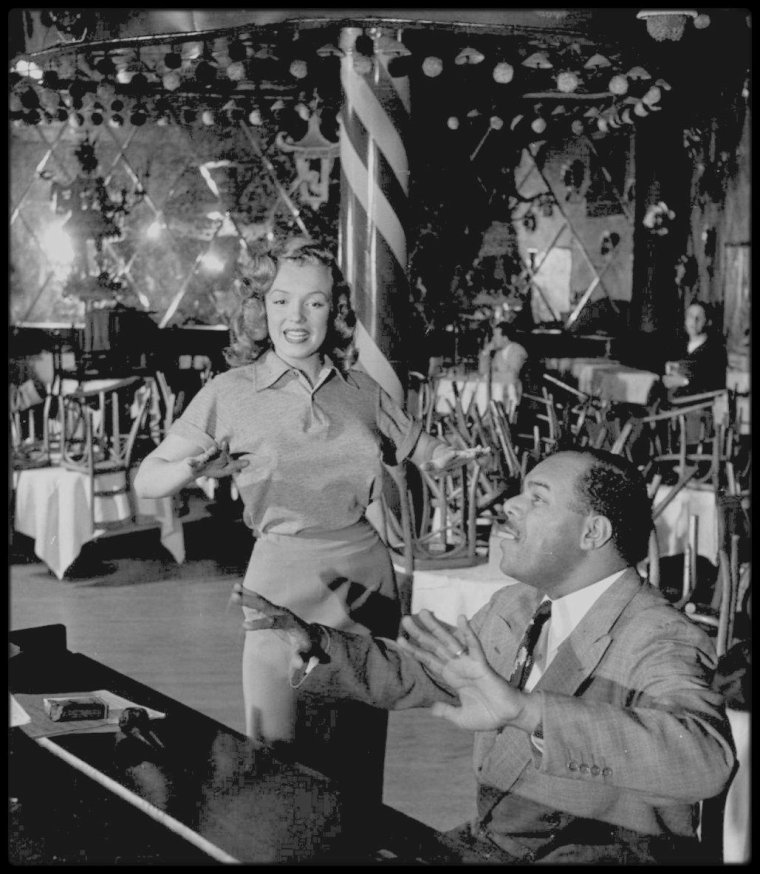 "1948 / Photos J.R. EYERMAN, Marilyn prenant des cours de chant au ""Mocambo Club"" aux côtés de Phil MOORE pour les numéros musicaux du film ""Ladies of the chorus"". Notons que Marilyn porte la robe du film ""Love happy""."