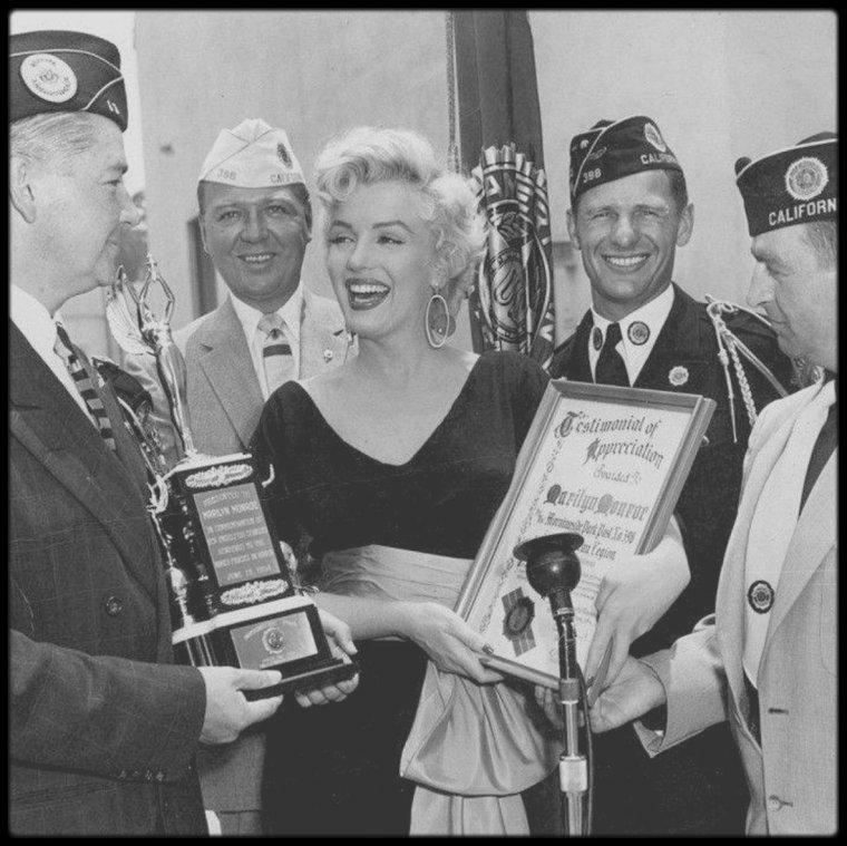 """19 Juin 1954 / Marilyn reçoit un trophée """"Testimonial Appreciation"""" décerné par """"The American Legion"""", lors du tournage du film """"There's no business like show business"""" à Morningside Park dans la ville d'Inglewood (en Californie), pour son soutien des troupes américaines en Corée où la star se produisit sur scène devant les GI's en février de la même année."""