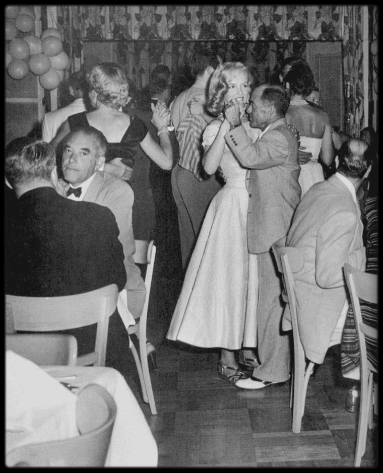 """1949-1950 / Johnny HYDE (Agent) : il avait 53 ans et rencontra Marilyn : - John CARROLL lui présenta Marilyn à une soirée du """"Racquet Club Resort Hotel"""" de Palm Springs.  - où ils firent connaissance à un réveillon du nouvel an chez le producteur Sam SPIEGEL ; à la fin de la soirée, HYDE aurait invité Marilyn à Palm Springs pour discuter de sa carrière. De rendez-vous en soirées passées ensemble, il tomba follement amoureux de Marilyn. C'était l'archétype du protecteur, celui qui grâce à ses brillantes relations, pouvait donner les orientations nécessaires à la carrière naissante de Marilyn. Dans le courant de l'année 1950 il quitta sa femme, Mozelle CRAVENS HYDE (actrice pour le """"Republic Pictures""""). Il loua une maison à Beverly Hills, mais Marilyn conserva quand même une chambre au """"Beverly Carlton Hotel"""". Il fit installer quatre banquettes en cuir dans la maison de North Palm Drive qu'il habita avec Marilyn ; la salle à manger possédait sa propre piste de danse, et Marilyn disait que cette pièce était son """"Romanoff"""" à elle. Sa secrétaire s'appelait Donna HOLLOWAY ; quand Marilyn était absente, Johnny HYDE lui demandait souvent de venir lui tenir compagnie, afin qu'il ne soit pas seul, vu qu'il souffrait de graves problèmes cardiaques. Il envoya Marilyn chez le Dr Michaël GURDIN, qui lui retoucha le nez et le menton; il lui fit teindre ses cheveux en blond platine, remonter la naissance de ses cheveux et réparer une petite imperfection dentaire. Il la pourvut d'une nouvelle garde-robe, et on la vit désormais à son bras dans tous les endroits à la mode . Il racheta le contrat qui la liait à son premier agent, Harry LIPTON, lui abandonnant un faible pourcentage sur les recettes, et se consacra corps et âme à transformer Marilyn en star. Il sollicita ses relations pour lui faire obtenir les rôles dont elle avait besoin. Il persuada Lester COWAN de l'engager pour son film avec les MARX Brothers, « Love happy » ; il organisa une audition à la Fox, ce qui lui valut un p"""