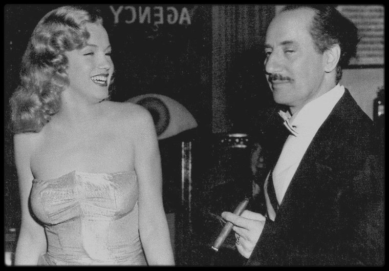 """1949 / Marilyn et Groucho MARX lors du tournage de """"Love happy"""", où elle fait une apparition furtive mais très glamour et remarquée ; Les récits des débuts de Marilyn à Hollywood sont si nombreux et si divergents qu'on ne peut connaitre avec certitude les circonstances exactes de sa rencontre avec les MARX Brothers. Le tournage eut lieu début 1949, mais des problèmes financiers repoussèrent la sortie du film à l'année suivante. Marilyn obtint une audition avec le producteur Lester COWAN par l'intermédiaire soit de Johnny HYDE, soit de son premier agent Harry LIPTON, soit encore de John CARROLL. Le film fut le dernier des MARX Brothers et le quatrième de Marilyn. Bien qu'on ne la vît que dans une seule scène, elle apparaissait au générique. Elle pénétrait dans le bureau de Groucho, qui était détective privé, dans une robe bustier moulante et son rôle se limita à quatre répliques. Elle fut payée 500 $ pour le rôle, plus 300 $ pour les photos publicitaires du film. Elle reçut encore 100 $ par semaine pour la tournée promotionnelle, ainsi qu'un forfait pour une nouvelle garde-robe."""