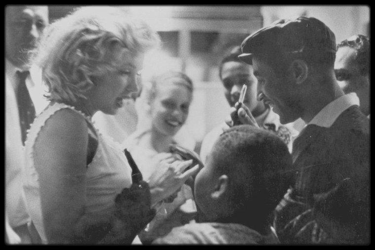 """1957 / Photos Sam SHAW, Marilyn sur la 5ème Avenue, N.Y., chez """"TIFFANY & CO"""", choisissant des vêtements pour son mari Arthur MILLER."""