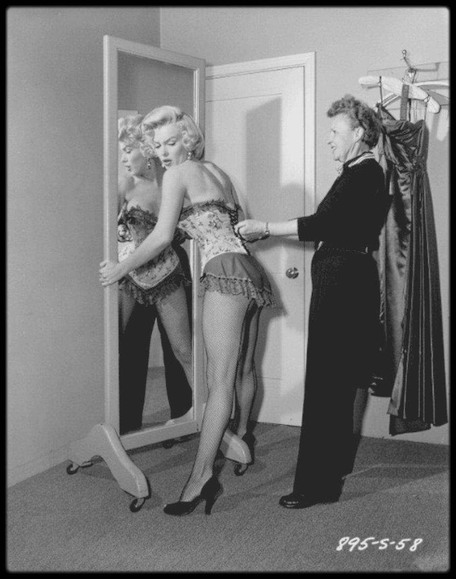 """1953 /  Marilyn, guêpière,corset et bas résille, en séance maquillage (notamment par Allan SNYDER) et habillage lors du tournage du film """"River of no return"""", ainsi que le coiffage avec Gladys RASMUSSEN."""