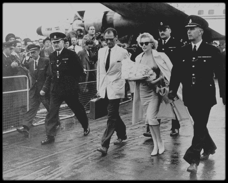 """14 Juillet 1956 / C'est sous une pluie fine que le couple MILLER-Marilyn arrive à l'aéroport de Londres pour le tournage du film """"The Prince and the showgirl"""" avec Laurence OLIVIER ; pas moins de 70 policiers étaient chargés de canaliser la foule et plus de 200 photographes qui les attendent."""