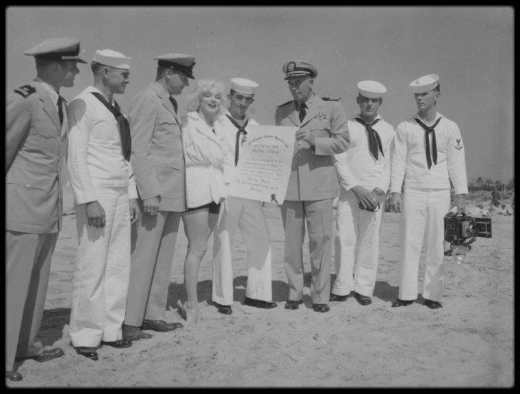 """1958 / Marilyn en peignoir lors du tournage de """"Some like it hot"""", sur la plage de """"l'Hotel Del Coronado"""", notamment avec sa coach Paula STRASBERG ou de son mari Arthur MILLER ; """"L'Hotel Del Coronado"""" (aussi connu comme """"The Del"""" ou """"Hotel Del"""") est un hôtel situé à Coronado, près de San Diego, en Californie, aux États-Unis. Hôtel de luxe, il jouxte directement la plage et donne sur la baie de San Diego. C'est l'un des rares exemples survivants d'un style d'architecture américaine typique : la station balnéaire victorienne en bois. C'est d'ailleurs l'un des plus anciens bâtiments en bois de Californie. Il est inscrit sur le """"National Register of Historic Places"""" depuis 1977 et est désigné monument historique en Californie."""