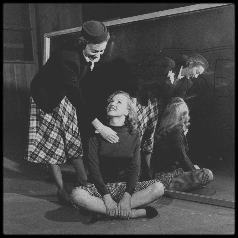 """1948 / Photos J R EYERMAN / La jeune Marilyn et son professeur d'art dramatique Natasha LYTESS, répétant pour le film """"Love happy"""" / A PROPOS DE MISS LYTESS / Elle jouait le rôle de mère et incarnait la stabilité aux yeux de Marilyn; elle s'investit dans la carrière de Marilyn à une époque où personne n'en eut le courage; elle aida Marilyn à développer et à exprimer ses talents et sa curiosité pour le monde du théâtre et de la culture générale. Dans certaines biographies, elle est décrite comme une femme amère, pleine de ressentiment. Il est vrai que, lorsque prit fin leur relation compliquée de maître à élève, le choc fut rude et douloureux pour elle. En terme de jeu théâtral, elle enseigna à Marilyn la subtilité des gestes, l'élocution, la diction et le souffle ; elle l'encouragea à parler de façon naturelle. Elle pensait que « le registre de la voix exprime la gamme des émotions humaines, car à chaque émotion correspond une modulation de la voix ».  Elle donna des cours intensifs à Marilyn avant chaque audition, et ce dès le premier instant de leur collaboration. Elles travaillèrent pendant trois jours et trois nuits afin de préparer la seconde audition de « The asphalt jungle » (1950), réalisé par John HUSTON. Quand Marilyn obtint le rôle, Natasha quitta la Columbia pour se mettre au service de Marilyn à plein temps. John HUSTON fut le premier réalisateur confronté à la totale dépendance de Marilyn envers Natasha : après chaque prise, elle regardait son professeur pour chercher approbation ou désapprobation. Cet instant est visible dans la première scène du film « The asphalt jungle » (1950). Quand Marilyn signa enfin son contrat de longue durée avec la Fox en 1950, la seule modification qu'elle apporta à son contrat fut d'y inclure Natasha LYTESS comme son professeur d'art dramatique personnel. Natasha gagnait 500 $ par semaine, plus 250 $ pour les cours privés qu'elle donnait à Marilyn (ce qui signifie que pendant sa première année à la Fox, Marilyn gagna moin"""