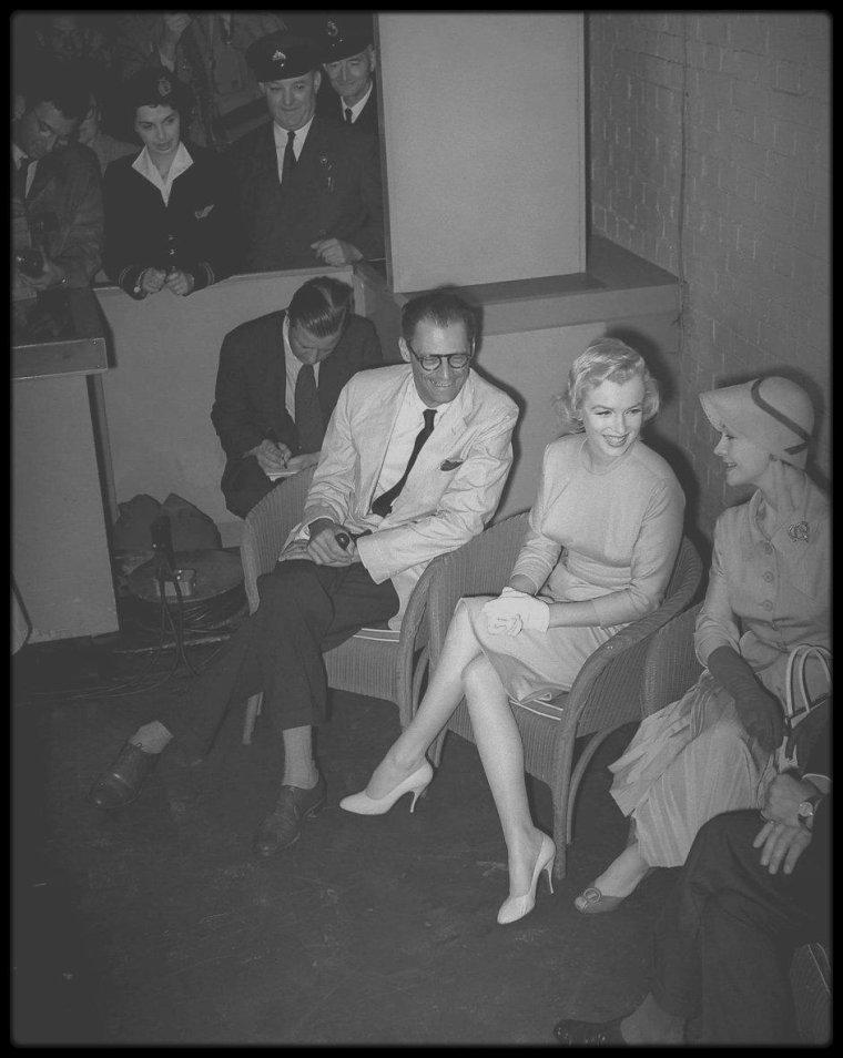 """14 Juillet 1956 / Marilyn et Arthur arrivent à l'aéroport de Londres, où les attendent Laurence OLIVIER et sa femme Vivien LEIGH, ainsi que des centaines de fans et autres policiers ; en effet, Marilyn rencontrera son futur partenaire Laurence OLIVIER, avec qui elle jouera dans le film """"The Prince and the showgirl"""". Une conférence de presse est alors organisée au sein même de l'aéroport. (part II)"""