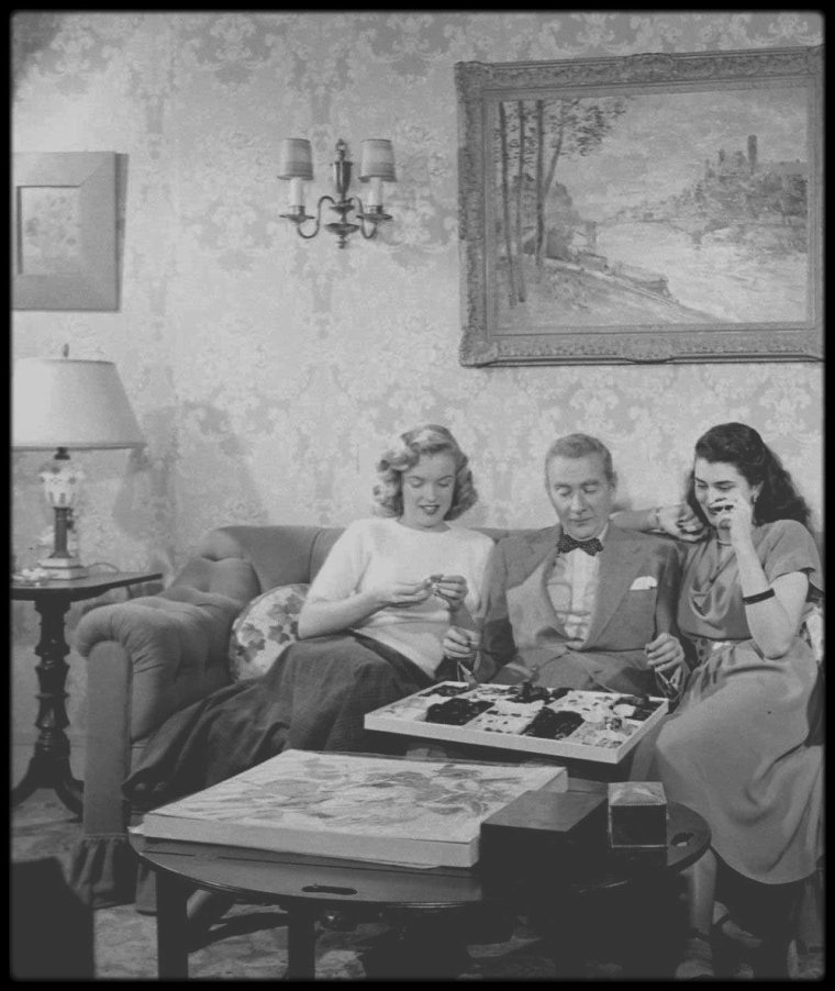 """1948 / C'est en visite dans les studios de la Fox, que Marilyn rencontre l'acteur Clifton WEBB et l'actrice Laurette LUEZ, alors qu'ils tournent une scène du film """"Sitting pretty"""" ; la jeune Marilyn se prête alors au jeu des photos, sous l'objectif du photographe Loomis DEAN, alors présent pour un reportage photographique."""