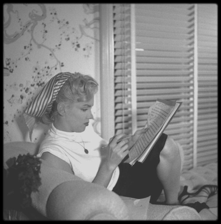 """1952 / Marilyn dans son dressing-room de la Fox, étudiant le script du film """"Niagara"""", sous l'oeil du photographe Earl THEISEN."""