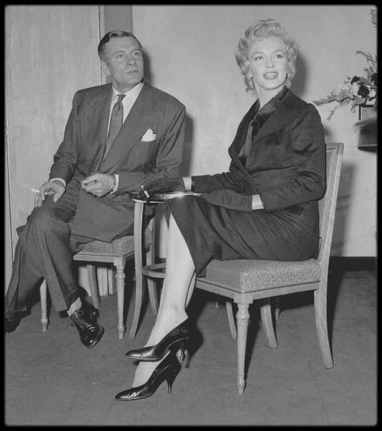"""16 Juillet 1956 / Une conférence de presse est donnée à l'Hôtel Savoy de Londres, entre Laurence OLIVIER et Marilyn, son futur partenaire dans le film """"The Prince and the showgirl"""". /A PROPOS / Une véritable guerre éclate entre Marilyn et Laurence OLIVIER, lors du tournage. La star est accompagnée de son coach Paula STRASBERG - l'épouse du fondateur de l'Actor's Studio, Lee STRASBERG - qui exige du metteur en scène d'interminables répétitions avant chaque prise. Excédé, OLIVIER exprime publiquement son impatience et sa colère et obtient enfin le départ de Paula STRASBERG. Mais le jeu de Marilyn ne lui convient pas pour autant. La star est vexée et se venge : retards, absences, maladies imaginaires, panique devant la caméra, prises ratés et recommencées jusqu'à épuiser le jeu d'OLIVIER."""