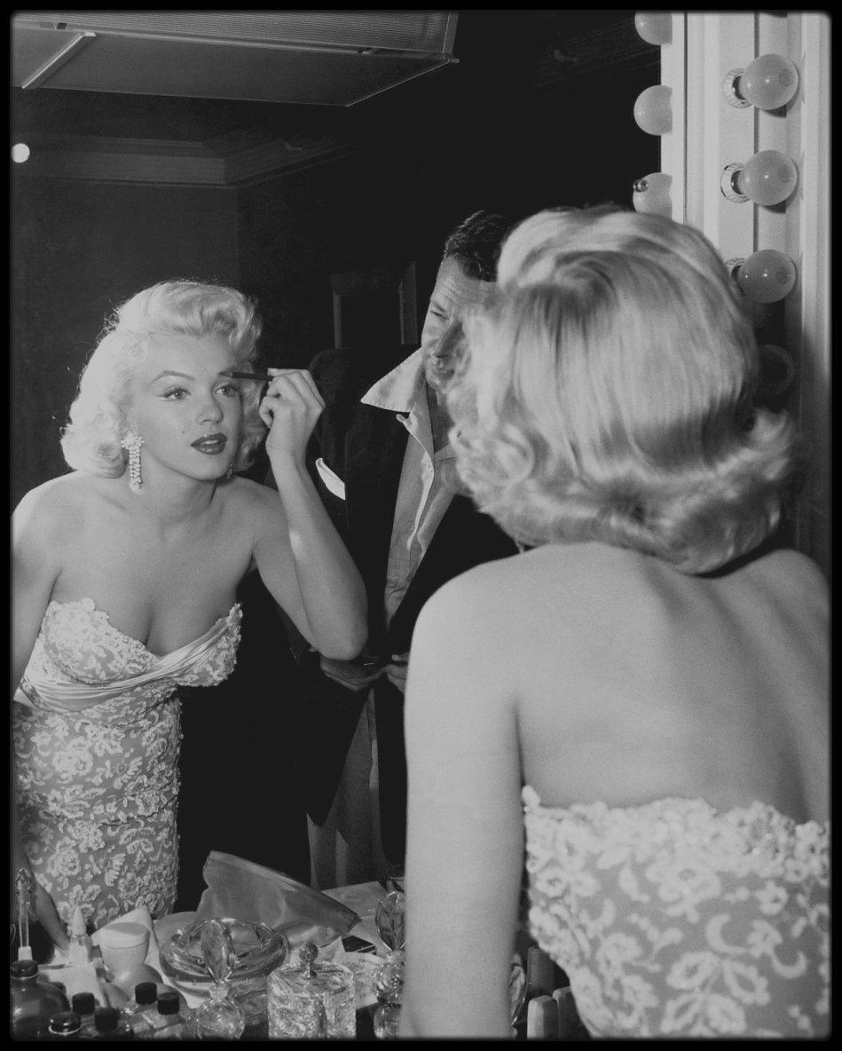 """POUR UNE SOIREE MESDAMES, JOUEZ VOUS LA... Marilyn ! / SECRETS DE BEAUTE / L'icône de beauté ne passait pas en 30 secondes de sa salle de bains aux feux des projecteurs ; elle passait d'abord par la case maquillage, et cela pouvait durer 3 heures. Poo poo pi doo !  /   LE CORPS /  Marilyn prenait des bains glacés pour raffermir sa peau. / LE VISAGE / Marilyn se nettoyait le visage avec l'huile démaquillante """"Cleansing Oil"""" de la marque """"Shu Uemura"""". Elle utilisait de l'huile d'olive pour nourrir sa peau. Avant d'appliquer son maquillage, Marilyn se protégeait le visage avec une épaisse couche de vaseline, de crème aux hormones (qui lui a d'ailleurs valu d'avoir un duvet blond sur tout le visage) et de crème Nivea afin d'hydrater sa peau. Elle évitait au maximum les fards et autres poudres matifiantes afin de garder un teint frais et « glossy ». Cependant, elle soulignait ses pommettes et sa mâchoire par un trait de poudre corail, et ajoutait ensuite de la poudre rose sur ses pommettes, sur la tempe et le nez. Une poudre plus claire était enfin appliquée sur les ailes du nez, l'arrête nasale et le bas du front. / LES YEUX / Elle appliquait un fard à paupières blanc mat sur la paupière supérieure jusqu'au sourcil pour ouvrir l'½il. Puis un fard à paupières blanc nacré sur la paupière supérieure mobile.  Elle utilisait un recourbe-cils, puis un mascara noir, puis ajoutait des faux-cils (eh oui !). Elle dessinait au pinceau marron un trait assez fin à la lisière des cils supérieurs afin d'intensifier son regard ; le trait se terminait en une courbe remontant légèrement vers les tempes. Elle appliquait un trait de poudre foncée dans le creux de la paupière supérieure, afin de donner de la profondeur à ses yeux.  Pour simuler l'ombre de ses immenses (et faux) cils, elle dessinait un fin trait de crayon noir et légèrement estompé sous les cils inférieurs, qui s'éloignait des cils de quelques millimètres sur l'extérieur de l'½il. Il y avait donc, à l'extérieur de chaque ½il"""