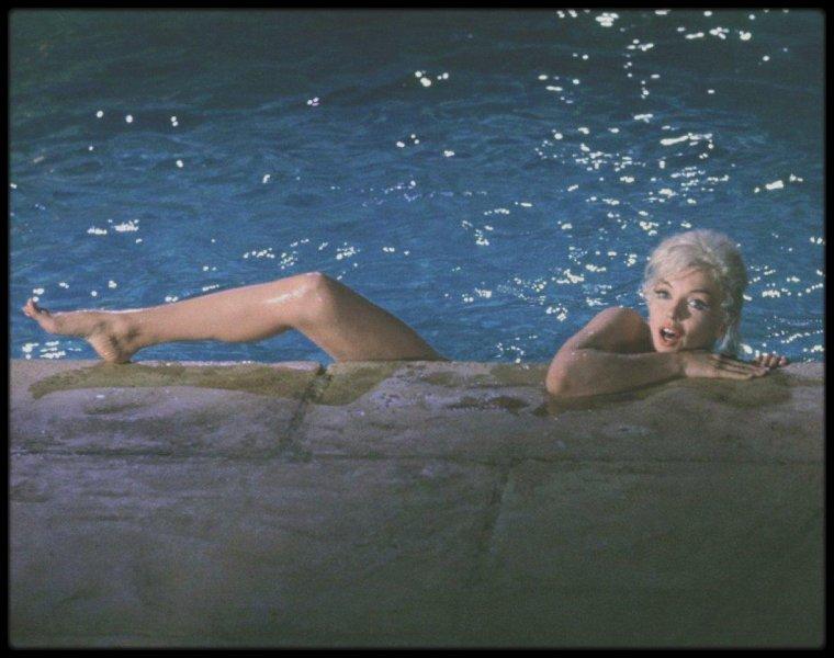 """1962 / Marilyn lors du tournage de """"Something's got to give"""" ; scène de la piscine, où elle se baigne portant un maillot de bain couleur chair, qu'elle enlèvera au fur et à mesure que le photographe Lawrence SCHILLER la photographiera. / Sur trente jours de tournage, Marilyn n'a été présente que treize jours. La Fox, à bout, l'a alors congédiée. Kim NOVAK et Shirley MacLAINE ont rejeté l'offre de succéder à Marilyn. Lee REMICK a accepté le rôle d'Ellen et Dean MARTIN s'est ainsi retiré de la production. Comme on allait l'accuser de faire perdre leur place de travail à une centaine de personnes et comme elle pressentait une menace sur sa carrière, Marilyn a lancé une campagne de relations publiques au travers d'interviews dans de nombreux magazines et de nouvelles photos et, à la suite de ce fort impact, la Fox lui a proposé une renégociation du contrat afin de pouvoir finaliser le film. Marilyn est décédée dans la nuit du 4 au 5 août 1962."""