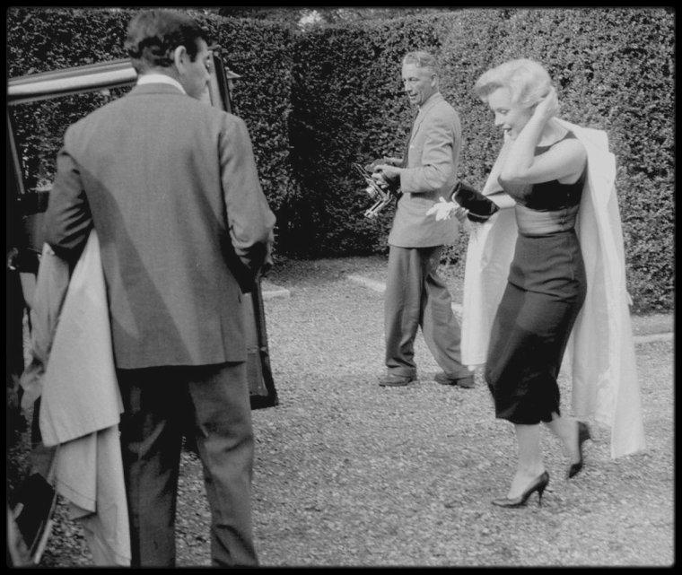 """15 Juillet 1956 / Le lendemain de leur arrivée à Londres, le couple MILLER se rend à Egham, où ils logeront dans un superbe manoir du XVIIIème siècle ; il comptait cinq chambres, une salle de séjour avec des poutres en chêne, deux salles de bains et  des chambres de service et était entouré d'un parc d'environ cinq hectares avec une roseraie. Dans cette maison, de lourds doubles rideaux avaient été installés aux fenêtres de la chambre de Marilyn, car elle ne pouvait dormir que dans le noir absolu. La chambre, à l'initiative de Milton GREENE, avait aussi été meublée de blanc (lit, rideaux, meubles, tapis) comme dans son appartement new-yorkais. Dans la plus pure tradition britannique, les journalistes assiégèrent le portail de la propriété durant tout leur séjour. Une séance photos est alors organisée dans le parc et sa roseraie. Ils se rendent ensuite à l'""""Hôtel Savoy"""" pour une conférence de presse avec Laurence OLIVIER, futur partenaire de Marilyn dans le film qu'ils vont tourner ensemble, """"The Prince and the showgirl""""."""