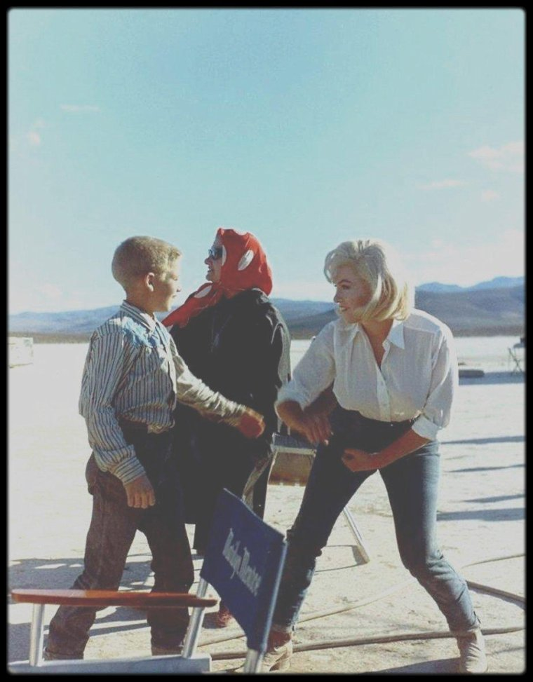 """1960 / Jeans et bottes pour Marilyn lors du tournage d'une scène du film """"The misfits"""". / Arthur MILLER évoque le tournage du film / """"Le tournage en était arrivé au point mort. À quoi bon transporter des dizaines de techniciens à travers la montagne jusqu'au lac Salé, alors qu'on ne savait abolument pas si l'on travaillerait ou non ? Nous étions en pleine crise. Quoi que Lee STRASBERG ait pu lui dire, cela n'avait apparemment eu aucun effet sur Marilyn, et maintenant il était reparti pour New York. Je montai alors voir Paula (épouse de Lee STRASBERG, et répétitrice de Marilyn). Elle me fit entrer dans son salon, un doigt sur les lèvres, puis s'avança vers la chambre à coucher, où je la suivis. Marilyn était assise dans le lit. Un médecin palpait son poignet, cherchant une veine pour lui faire une injection d'Amytal. Mon estomac se retourna. Elle me vit et me cria de sortir. Je parvins à demander au médecin s'il savait quelle quantité de barbituriques ou autres médicaments elle avait déjà incurgitée, et il me regarda d'un air désemparé, il n'était qu'un jeune homme effrayé qui voulait seulement faire sa piqûre, partir et ne jamais revenir... Une seule chose était certaine. Marilyn devait terminer le film. Échouer confirmerait la pire de ses angoisses, la peur de perdre le contrôle de sa vie, de passer sous la vague de fond d'un terrible passé. Elle dormait. Une fois de plus, je regrettai de ne pas savoir prier et de ne pouvoir invoquer l'image de celui qui ne connaît que l'amour. Mais pour cela aussi, il était trop tard. HUSTON prit le taureau par les cornes et organisa le transport de Marilyn dans un hôpital privé de Los Angeles où elle se déshabituerait des barbituriques avec le secours de son analyste. Dix jours après, elle était de retour - son incroyable résistance me paraissait maintenant presque héroïque -, l'air merveilleusement maîtresse d'elle-même, quoique ses yeux n'eussent pas encore recouvré leur brillant. Cela aussi reviendrait sans doute, à condition """