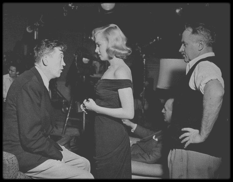 """Automne 1949 / Tournage du film """"The Asphalt jungle"""" de John HUSTON (film qui sortira en 1950), qu'elle retrouvera dix ans plus tard pour """"The misfits"""" ; Durant toute la durée du tournage, Marilyn refusa de jouer la moindre scène sans Natasha LYTESS. Le résultat fut absolument fabuleux, malgré la présence continuelle de Natasha sur le plateau. Aux dires de HUSTON et HORNBLOW, après chaque prise de vue, Marilyn consultait du regard son professeur, et cette dernière hochait ou secouait la tête pour lui signaler sa satisfaction ou sa désapprobation. Ses constantes interventions en sous-main rendirent Natasha extrêmement impopulaire auprès du réalisateur. Natasha et Marilyn mirent au point une série de signes de la main, qui permettaient de savoir si elle jouait de façon conforme aux répétitions. Le fait de jouer sous le regard impitoyable de son coach avait exacerbé la sensibilité de Marilyn. Toutefois, sa dépendance vis-à-vis de son professeur n'empêcha pas Marilyn de jouer admirablement. Sa performance, éblouissante, laissait penser que d'autres propositions plus importantes allaient suivre.  Avec ce film, Marilyn, considérée jusqu'alors comme une débutante, gagna le titre d'actrice. Son nom apparu dans le  générique de la fin, parmi les autres rôles secondaires."""