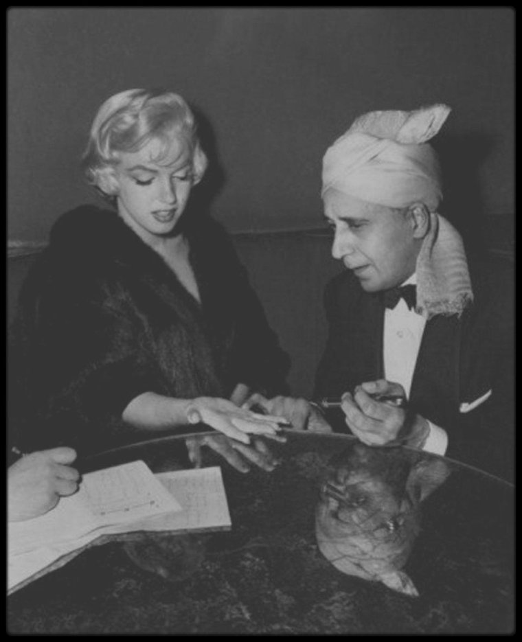 """2 Décembre 1954 / Marilyn donne une interview au """"Beverly Hills Hotel"""", accompagnée du jeune acteur Robert WAGNER, à la journaliste Maria ROMERO ; à cette occasion, Marilyn rencontre le médium Hassan, qui lui lira les lignes de la main."""