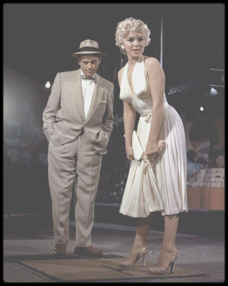 1954 / TOURNAGE DE LA SCENE CULTE (Part II) / « The seven year itch » fut le dernier film que Marilyn tourna pour la Fox sous « l'ancien régime » - contrat très restrictif et salaire pitoyable (pour les standards hollywoodiens). Cela faisait longtemps qu'elle avait repéré les qualités de cette pièce, qui avait obtenu un grand succès à Broadway. Marilyn accepta même de jouer dans un film moins attrayant, « There's no business like show business » (1954), à condition que la Fox achète les droits de la pièce de George AXELROD, pour un montant de 500 000 $, dit-on. Le tournage de « There's no business like show business » ayant pris du retard, elle dût enchaîner directement avec « The seven year itch », le 10 août 1954. Billy WILDER et AXELROD avaient alors entièrement récrit le scénario et modifié la fin. Dans la version théâtrale, les personnages deviennent amants, mais dans le film, la vertu l'emporte. Tom EWELL, qui avait tenu le rôle sur les planches à Broadway, incarne un new-yorkais dont l'imagination s'enflamme au cours d'un long et chaud été, alors que sa femme et son petit garçon sont partis en vacances. L'irruption de sa nouvelle voisine du dessus, une blonde pulpeuse, chamboule son univers. Ce personnage interprété par Marilyn, est la reine des ingénues : elle met ses dessous au réfrigérateur pour avoir un peu de fraîcheur, reconnaît la musique classique au fait qu'il « n'y ait pas de chant » et arrive à dégager un charme des plus mutins sans même réaliser l'effet qu'elle produit. Curieusement, dans le film, le personnage de Marilyn n'a pas de nom. Au générique elle est simplement « la fille ». Voici ce que répondit George AXELROD lorsqu'on lui demanda ce que cela signifiait : « Le fait est que je n'ai jamais pu lui trouver un nom qui convienne, qui colle vraiment à la fille que j'avais en tête. »  Dans ce film, Marilyn arbore dix toilettes différentes. Le styliste William TRAVILLA acheva en un seul week-end tous ses croquis préliminaires, y compris celui de