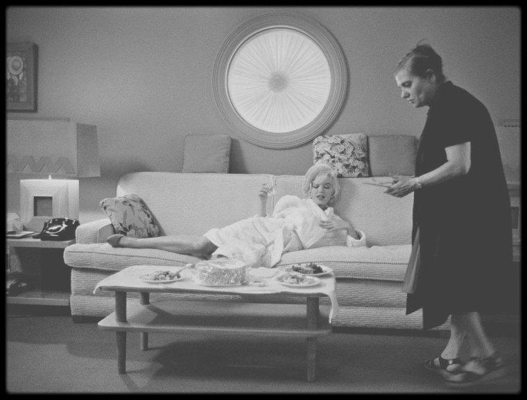 """1962 / Marilyn en pause, notamment dans sa loge avec Paula STRASBERG lors du tournage du film """"Something's got to give"""" (Certaines photos signées Lawrence SCHILLER) / La naissance même du film n'a rien du rêve hollywoodien. Marilyn, en contrat avec la 20th Century Fox, n'a pas tourné avec les studios depuis deux ans et leur doit encore un film. La Fox est au bord de la faillite avec les retards et dépassements du tournage titanesque de """"Cléopâtre"""" de Joseph L. MANKIEWICZ à Rome. Un film avec Marilyn en tête d'affiche apparaît comme la solution idéale pour renflouer des caisses qui se vident dangereusement. Le choix se porte alors sur le remake d'un film de 1940 : """"My Favorite Wife"""" de Gardon KANIN avec Irene DUNNE et Cary GRANT. Comme souvent à Hollywood, le choix du réalisateur n'intervient qu'après celui de l'histoire et de l'acteur principal. Marilyn soumet en 1961 à la Fox une liste de dix réalisateurs avec lesquels elle accepterait de tourner, parmi lesquels : WILDER, KAZAN, HUSTON, FORD, MANKIEWICZ, HITCHCOCK… Le choix se portera sur George CUKOR, avec qui l'actrice a déjà tourné """"Le Milliardaire"""" (1960). Ce précédent tournage s'étant assez mal déroulé, CUKOR est plus que réticent. Mais une menace de procès pour rupture de contrat et un beau salaire sauront convaincre le réalisateur. Reste à achever le scénario, source de toutes les tensions, Marilyn ayant trouvé la première ébauche « insipide ». Elle approuve la version de Nunnally JOHNSON, que refuse CUKOR qui adjoint Walter BERNSTEIN au projet. Le retard s'accumulant, le tournage commence avant la fin de l'écriture du scénario et sa validation par toutes les parties. Il débute en mai pour une sortie du film à l'automne. Dean MARTIN et Cyd CHARISSE complètent la distribution pour ce film au casting quatre étoiles. On connaît la suite : l'actrice malade constamment absente, le planning de tournage sans cesse revu, le retard qui s'accumule… Au bout de huit semaines, il s'interrompt et l'actrice est renvoyée pa"""
