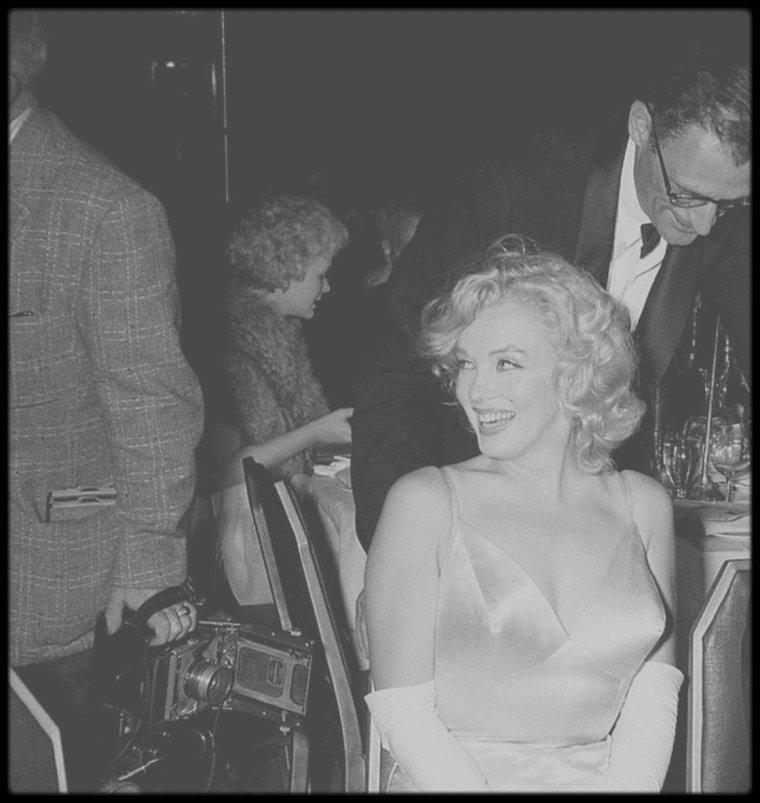 """13 Juin 1957 / (Part II) Marilyn et MILLER se rendent à la Première du film """"The Prince and the showgirl"""" au """"Radio City Music Hall"""" de New York ; comme toujours lorsqu'elle apparaît en public, Marilyn est éblouissante. Arthur MILLER, lui, à davantage de mal à dissimuler ses soucis : harcelé depuis plusieurs années par la Commission des activités antiaméricaines, qui l'accuse de communisme, il vient de comparaître une nouvelle fois devant le Congrès, à Washington. Dans la presse du lendemain, Marilyn sera couverte d'éloges pour sa prestation dans le film de Laurence OLIVIER, """"Le Prince et la danseuse"""" : """"En tant qu'individu et de comédienne, elle n'a jamais été aussi sûre d'elle même ; elle fait rire sans jamais sacrifier Marilyn à la véritable actrice ; c'est le propre des grands artistes de talent.La surprise est d'autant plus agréable que jusqu'ici, Marilyn MONROE a été moitié actrice, moitié phénomène"""" écrit le critique du """"New York Post"""". (Photos Paul SLADE)."""