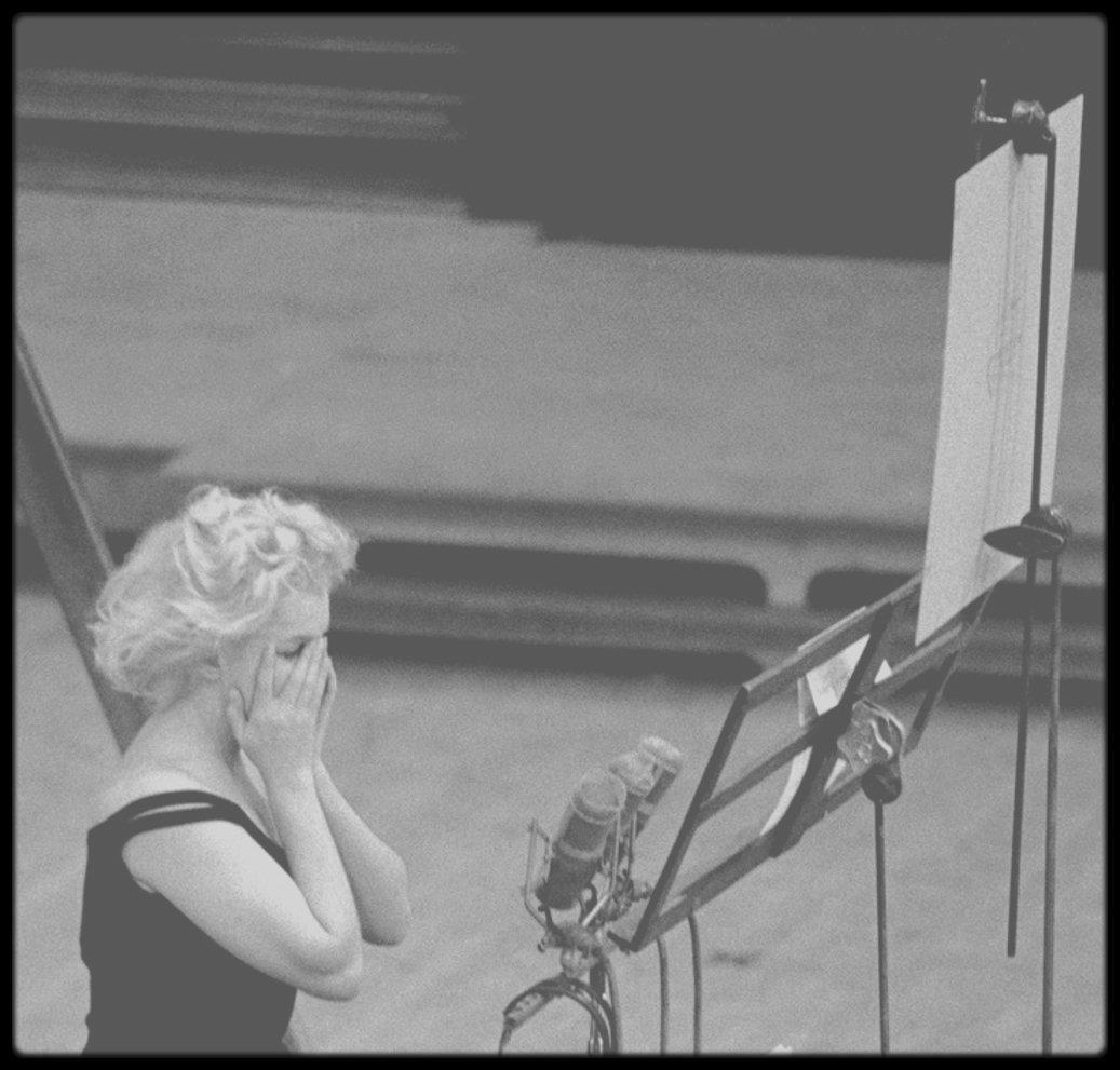 """1959 / Marilyn enregistrant les chansons du film """"Let's make love"""". (Photos Bruce DAVIDSON). Son professeur de chant et de danse n'était autre que Jack COLE ; Il créa les chorégraphies de toutes les chansons et numéros de danse de Marilyn dans « Gentlemen prefer  blondes » (1953), « River of no return » (1954), « There's no business like show business » (1954), « Let's make love » (1960). Il l'aida de façon anonyme à interpréter « Running wild » dans « Some like it hot » (1959). Elle avait une confiance absolue et implicite en lui, et ils devinrent immédiatement amis. Son rôle était celui d'un professeur qui la guidait pas à pas pendant les tournages; il se tenait à côté de la caméra et exécutait les pas pour Marilyn qui le regardait et le copiait comme dans un miroir. Il travailla particulièrement dur avec elle dans « Let's make love », car elle craignait les numéros de danse. Elle lui témoigna sa gratitude en lui donnant une enveloppe contenant 1 500 $ et un mot disant : « J'ai été insupportable et j'ai dû vous faire passer de mauvais moments. Prenez quinze jours de vacances dans un endroit agréable et oubliez tout ». Deux jours plus tard il reçu un autre chèque de 500 $ et un mot disait « Restez trois jours de plus »."""