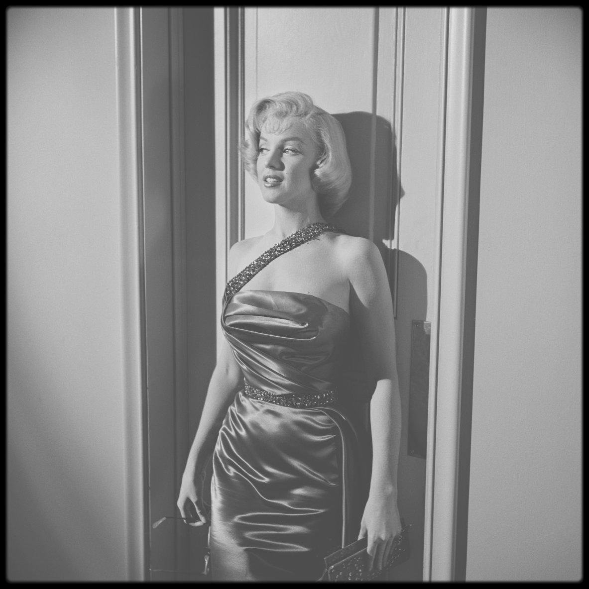 """1953 / (Photos Frank WORTH) Dans les coulisses du film """"How to marry a millionaire"""" ; La Fox sortit son brelan d'as, Betty GRABLE, Marilyn et Lauren BACALL, pour un film contant l'histoire de trois aventurières en chasse d'un riche mari. Le studio était fier de son premier film en Cinémascope avec trois stars en tête. Le scénariste Nunnally JOHNSON précisa qu'il avait crée les personnages en les adaptant à la personnalité des trois actrices. Malgré les efforts des studios pour « vendre » à la presse une guerre entre Marilyn et Betty GRABLE, les deux actrices s'entendirent fort bien. Betty GRABLE avait été l'idole de la nation pendant dix ans et passait gentiment le flambeau. Au départ, Marilyn revendiqua le rôle de Loco, attribué à Betty GRABLE, car elle n'aimait pas son propre personnage, Pola, affublée de lunettes. Jean NEGULESCO, le réalisateur, la persuada d'accepter, faisant valoir que c'était le meilleur rôle ; en effet, la drôlerie engendrée par la myopie, valut à Marilyn des critiques positives sur ses talents comiques. Pourtant, Marilyn ne considérait pas son interprétation comme l'une des meilleures. Au bout de quelques mois, le film avait fait une recette brute cinq fois supérieure à son extravagant budget de 2.5 millions de $."""