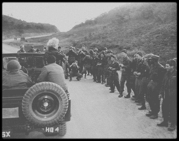 """1954 / Le 15 Février 1954, Marilyn """"interrompt son voyage de noces au Japon"""" avec le célèbre et populaire joueur de base-ball Joe DiMAGGIO """"pour aller chanter en Corée auprès des GI. Cette tournée durera quatre jours. Que racontent les images tournées par les cameramen de l'armée américaine ?"""" Le  couple DiMAGGIO se rend au Japon en raison du contrat signé par le champion retraité pour effectuer des démonstrations de ce sport et des séances d'entrainement de l'équipe japonaise au pays du Soleil levant. Les relations entre Marilyn et la Fox, dont elle est l'une des vedettes, sont alors tendues. Le 1er février 1954, le couple est accueilli par les fans du champion et de la star à son arrivée à l'aéroport nippon. En raison de la guerre de Corée, plus de 120 000 GI's sont stationnés dans cet Extrême-Orient. A Tokyo, Marilyn se rend auprès de soldats américains soignés dans des hôpitaux à Tokyo : elle est filmée serrant notamment la main de soldats noirs, mais ces images ne seront pas diffusées aux Etats-Unis.  En pleine Guerre froide, à la demande de l'Armée américaine, Marilyn se rend à Séoul, capitale de la Corée du sud, à plus de 1000 km du Japon. But : remonter le moral des plus de 100 000 soldats américains, basés pour la plupart au nord de Séoul, dans des camps le long de la frontière avec la Corée du nord : quelques années après la guerre de Corée, 18 divisions américaines et sud-coréennes sont installées le long de la frontière, sur moins de 300 km, de l'autre côté, sept corps des armées chinoises et deux divisions nord-coréennes. L'actrice Betty HUTTON en 1952, Joe DiMAGGIO et son ami joueur de baseball Lefty O'DOUL l'y avaient précédée pour des tournées militaires. Délaissant robe et manteau de fourrure, mais gardant de jolies boucles d'oreilles, la star est vêtue d'un uniforme militaire au col largement ouvert  à son arrivée en Corée. Cette tournée réunit la chanteuse et ses amis, des musiciens militaires, une infirmière aux armées. Des hélicoptères amènent l"""