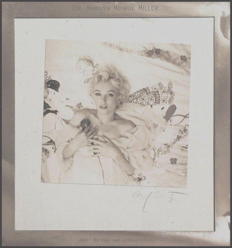 """22 Février 1956 / HISTOIRE D'UNE PHOTO / Le 22 février 1956 Marilyn pose devant l'objectif de Cecil BEATON pour le magazine """"Harper's Bazaar"""". Trois mois durant le photographe avait tout fait pour obtenir un rendez-vous. Ils se retrouvent dans une suite de l'hôtel """"Ambassador"""" de New York. Comme à son habitude, Marilyn arrive avec une heure et quart de retard. C'est lors de cette séance que BEATON prit le cliché préféré de Marilyn d'elle-même: enroulée dans une étole rose et allongée dans un lit aux draps blancs, elle tient un oeillet rouge sur sa poitrine.  Elle avait d'ailleurs encadrée cette photo -en noir et blanc- dans son appartement new-yorkais situé au 444 East 57th Street (photo), faisant parti d'un triptyque, accompagnée d'une lettre élogieuse du photographe."""